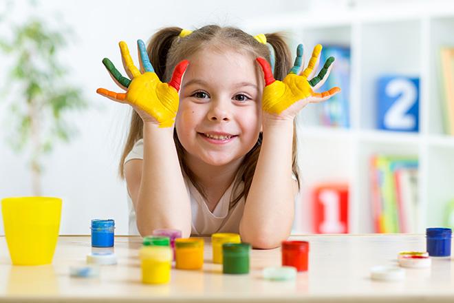 Niña en un aula, apoyada en un pupitre, con expresión alegre mostrando sus manos pintadas de colores