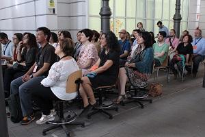 Decenas de personas sentadas escuchando una presentación.