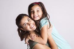 Una mujer sonriente coge en brazos a una niña