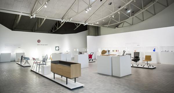 Sala de una exposición con sillas, muebles y otros objetos.