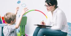 Una mujer con gafas a punto de escribir lo que le está contando un niño con los brazos levantados