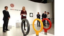 Exposición RED DOT AWARDS en Zaragoza. En primer plano un objeto de la exposición. Al fondo Marta Gascón dirigiéndose a los presentes.
