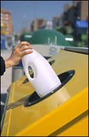 Una persona depositando un bote de plástico en el contenedor amarillo