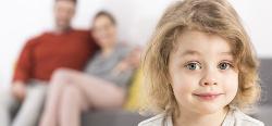 Primer plano de una niña con gesto sonriente y un segundo plano desenfocado de una pareja sentada en un sofá