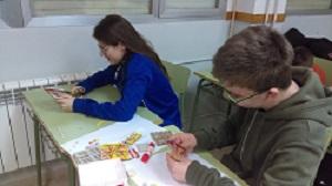 Dos alumnos hacen una manualidad con papel y pegamento.